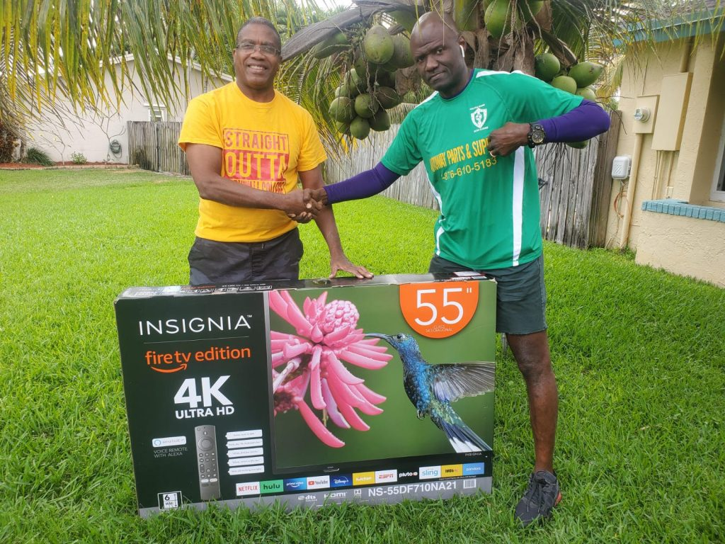 President Phillip Wallace presenting the winning prize of a 55 inch LED 4K UHD Smart TV to Garnett Denton who is the lucky winner of the Drive By Fish Fry raffle