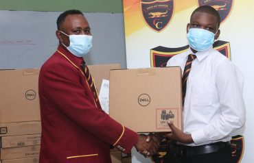 Dr. Richard Meghoo, President of the Montego Bay Chapter of the Old Boys Association presenting one of the machines to a student of Cornwall College